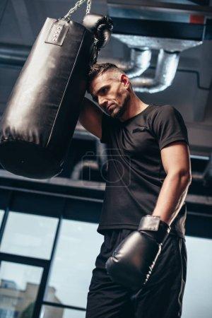 Photo pour Faible angle vue du beau boxeur fatigué se penchant sur le sac de boxe dans la salle de gym - image libre de droit