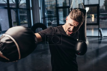 handsome boxer exercising with trainer and screaming in gym