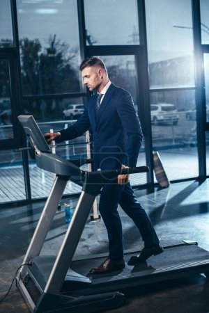 Photo pour Bel homme d'affaires en costume, exercice sur tapis roulant en salle de gym - image libre de droit