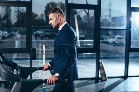 Photo pour Vue de côté du bel homme d'affaires en costume exercice sur tapis roulant dans la salle de gym - image libre de droit