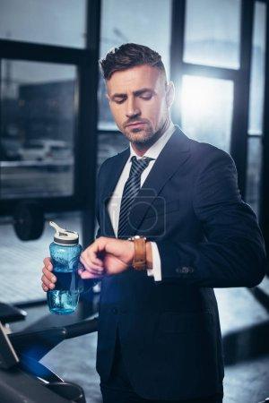 Photo pour Bel homme d'affaires en costume faisant de l'exercice sur tapis roulant, tenant une bouteille de sport et vérifiant le temps dans la salle de gym - image libre de droit
