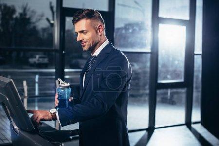 Photo pour Bel homme d'affaires en costume exercice sur tapis roulant et tenant bouteille de sport dans la salle de gym - image libre de droit