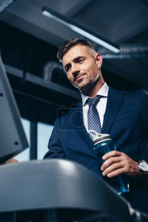 Photo pour Vue faible angle de bel homme d'affaires en costume, exercice sur tapis roulant et en maintenant la bouteille de sport en salle de gym - image libre de droit