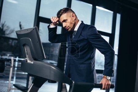 Photo pour Vue latérale de fatigué beau homme d'affaires en costume exercice sur tapis roulant dans la salle de gym - image libre de droit