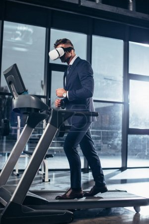 Photo for Side view of businessman in suit and virtual reality headset exercising on treadmill in gym - Royalty Free Image