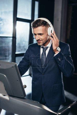 Photo pour Bel homme d'affaires en costume, exercice sur tapis roulant et l'écoute de musique avec des écouteurs dans la salle de gym - image libre de droit
