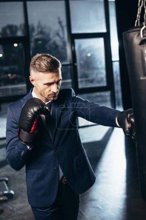 Photo pour Bel homme d'affaires en costume de boxe dans la salle de gym - image libre de droit