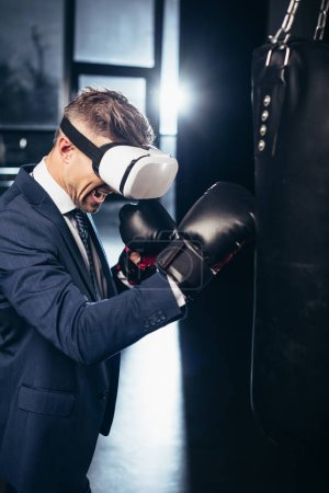 Photo for Businessman in suit and virtual reality headset boxing and screaming in gym - Royalty Free Image