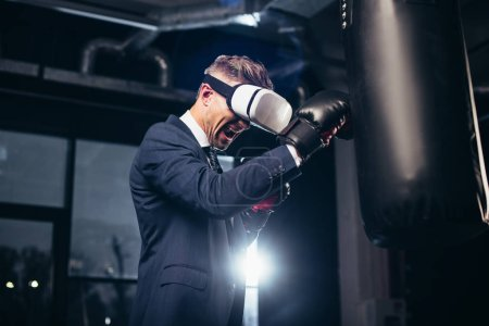 Photo for Low angle view of businessman in suit and virtual reality headset boxing and screaming in gym - Royalty Free Image