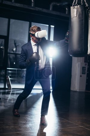 Photo for Businessman in suit and virtual reality headset boxing in gym - Royalty Free Image