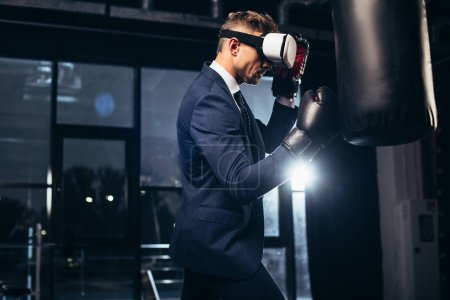 Photo for Side view of businessman in suit and virtual reality headset boxing in gym - Royalty Free Image