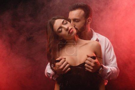 schöner leidenschaftlicher Mann zieht seine Freundin in einem rot verrauchten Zimmer aus
