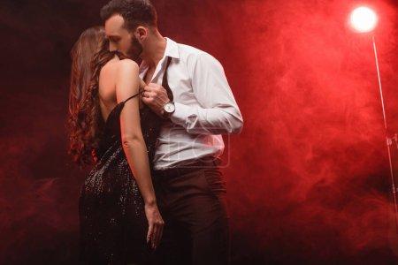 passionnée couple séduisant dans une pièce enfumée rouge