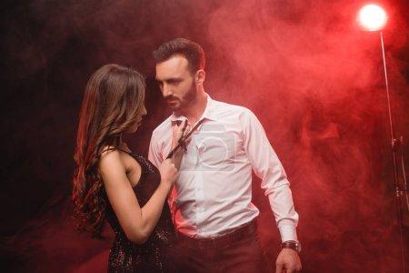 couple passionné dans une pièce enfumée rouge