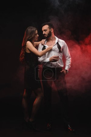 passionate woman hugging man with glass of whiskey in red smoky room