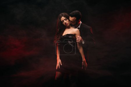 handsome man hugging seductive woman in red smoky room