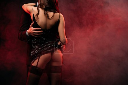 rear view of sexual couple hugging in red smoky room