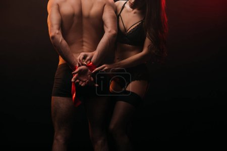 cropped view of sexy couple with red ribbon in smoky room