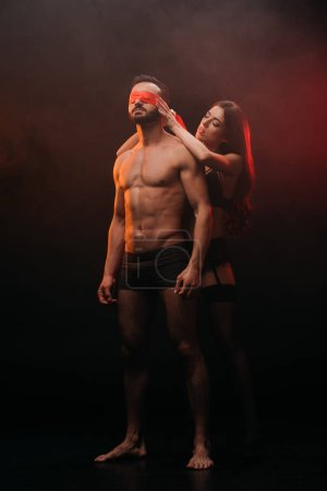 beautiful girl closing eyes of shirtless boyfriend with red ribbon in smoky room