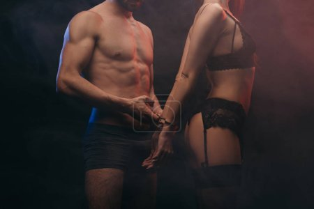 cropped view of erotic couple with handcuffs in smoky room