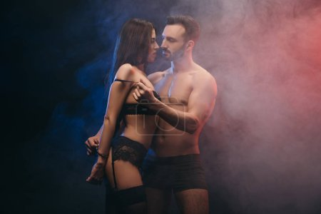 passionate loving couple with handcuffs in smoky room