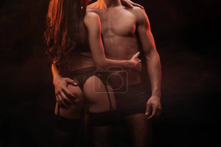 cropped view of sensual passionate couple hugging isolated on black