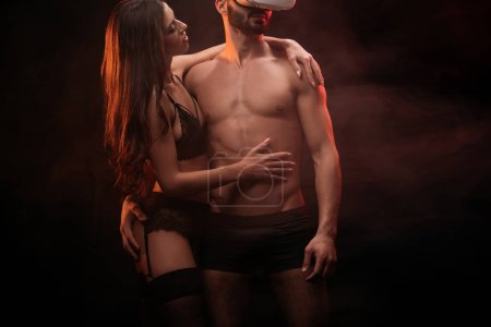 beautiful sexual couple in vr headset in smoky room