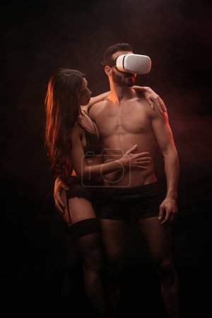 Photo for Beautiful erotic couple in virtual reality headset in smoky room - Royalty Free Image