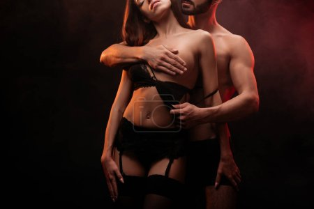cropped view of man undressing girl in lace bra isolated on black