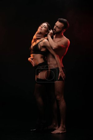 sensual passionate couple hugging isolated on black