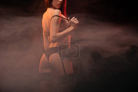 cropped view of seductive girl in black lingerie posing in dark smoky room