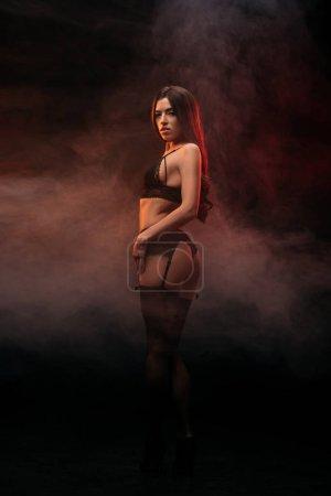 Photo pour Belle jeune femme sexuelle en lingerie noire posant dans la chambre sombre fumée - image libre de droit