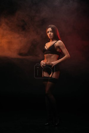 sexual young woman posing in lace lingerie in smoky room
