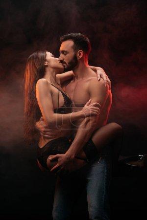 beau couple passionné étreintes et les baisers dans la salle enfumée
