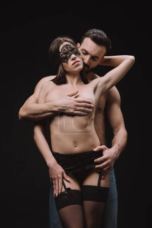 passionate man hugging sensual naked girlfriend in lace mask, isolated on black