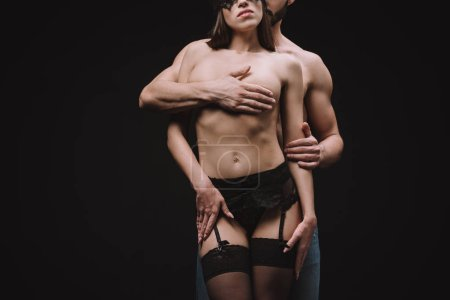 cropped view of sexual man hugging nude breast of beautiful girlfriend, isolated on black