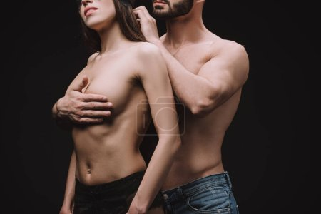 cropped view of man hugging nude breast of beautiful girlfriend, isolated on black