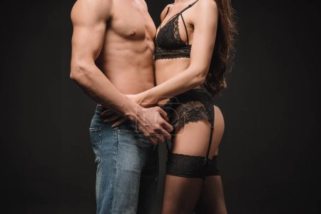 cropped view of seductive couple hugging isolated on black
