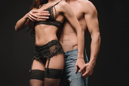 cropped view of sexual man hugging girl in lace lingerie isolated on black