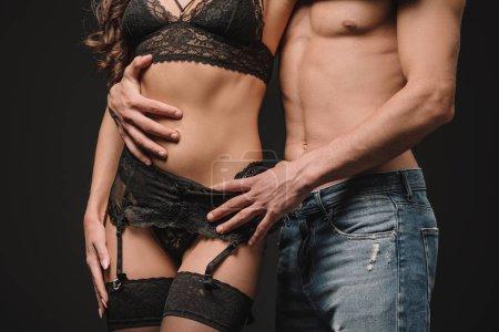 abgeschnittene Ansicht eines sexuellen Paares, das sich isoliert auf Schwarz umarmt
