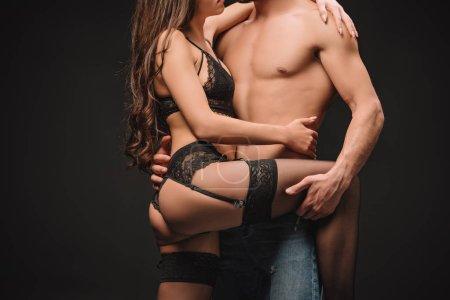 Photo pour Vue recadrée de couple érotique étreinte isolé sur noir - image libre de droit