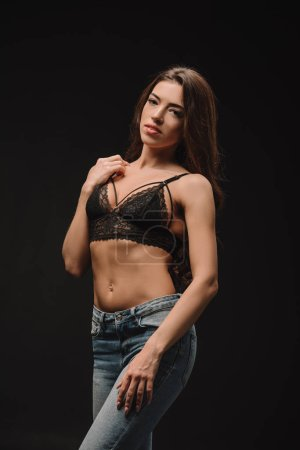 attractive girl posing in lace bra isolated on black
