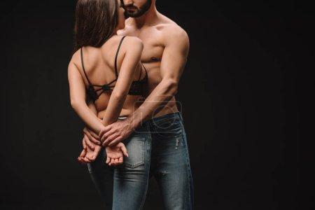 Photo pour Vue recadrée de beau couple passionné étreignant isolé sur noir - image libre de droit