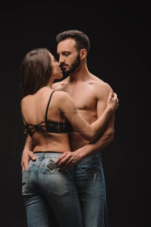 handsome shirtless man hugging girlfriend and holding condom isolated on black
