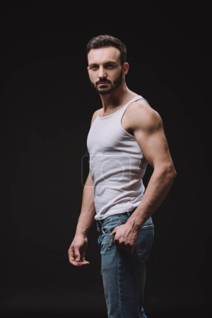 sexy handsome man posing in white singlet isolated on black
