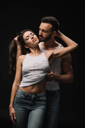 passionate man undressing girl in white singlet isolated on black