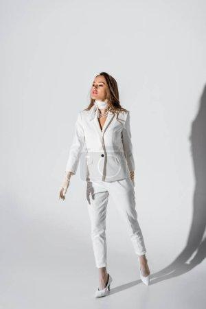Photo pour Jolie jeune fille en costume et gants posant sur fond blanc - image libre de droit