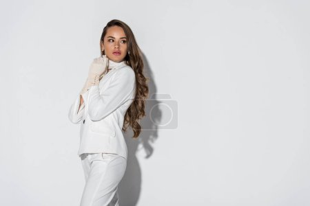 Photo for Attractive girl with long hair in suit standing on white background - Royalty Free Image