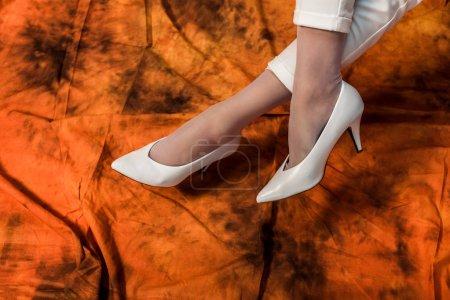 Photo pour Vue recadrée des jambes féminines en chaussures blanches sur fond abstrait - image libre de droit
