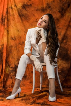 attractive girl with long brown hair in white suit sitting on chair on textured background